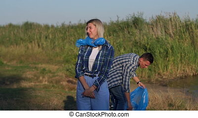 Volunteer team collecting rubbish outdoors and having fun. Work break concept.