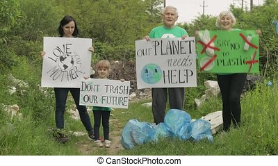 Volunteer activist team holding encouraging posters. Calls out slogans around plastic bags bottles in park background. Reduce trash nature cellophane pollution. Earth eco recycle rubbish. Save ecology