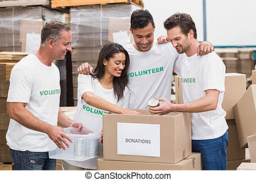 Volunteer team packing a food donation box in a large warehouse