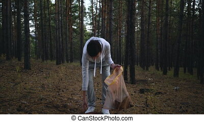 volunteer with garbage bags cleaning forest.