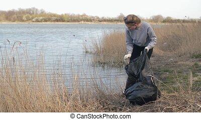 Woman putting waste into bin bag