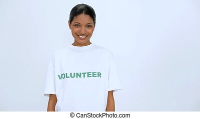 Volunteer woman smiling and does a thumb up at camera on white background