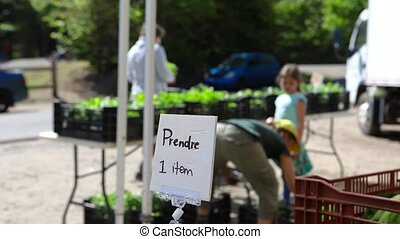 Blurry people are seen at a local farmer's market behind a sign saying pick one item, as farmer gives surplus produce to the local community, with copy-space.