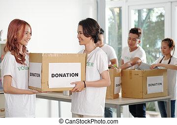 Volunteers carrying box