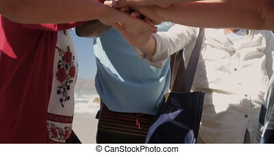 Volunteers forming hand stack on the beach 4k