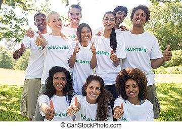 Volunteers gesturing thumbs up - Group portrait of confident...