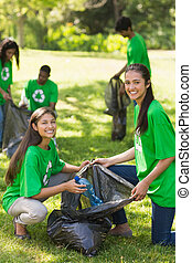 Volunteers picking up litter in par - Team of young...