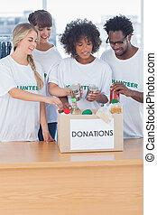 Volunteers putting food in donation box