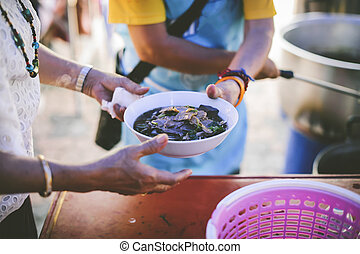 Volunteers scooping the food to share with the needy : concept of free food to beggars