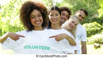 Volunteers standing in a row giving smiling at camera on a...