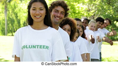 Volunteers standing in a row giving thumbs up to camera on a...