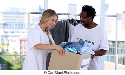 Volunteers storing clothes - Two young volunteers storing...