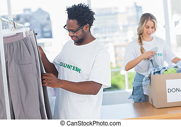 Volunteers taking clothes out of a donation box