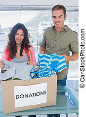 Volunteers taking out clothes from a donation box