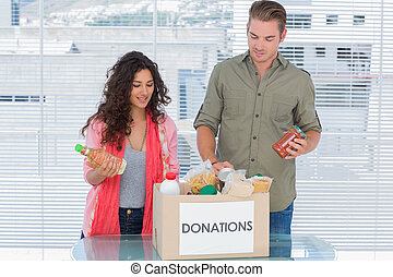 Volunteers taking out food from donations box