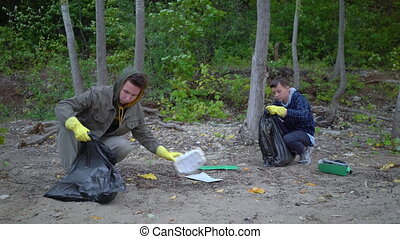 volunteers with garbage bags cleaning forest.