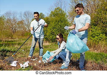 volunteers with garbage bags cleaning park area -...