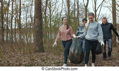 Volunteers with garbage bags walk in the park - Young ...