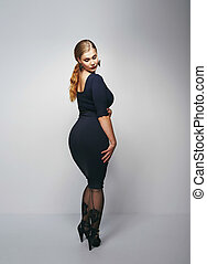 Voluptuous woman posing in black dress - Studio shot of...