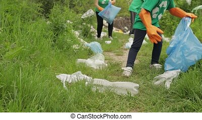 Close up voluteers activists child girl in green t-shirt, gloves tidying up bags, bottles rubbish in forest. Save environment stop plastic cellophane pollution. Recycle ecology garbage nature altruism