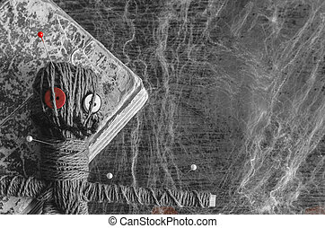 Voodoo doll with needles and old book on wooden background covered with spiderweb