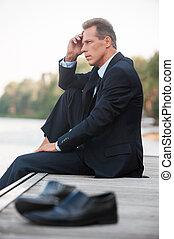 voorgrond, over, zijn, blootsvoets, schoentjes, zittende , weg, aanzicht, het leggen, business., hand, het kijken, quayside, nadenkend, kin, vasthouden, zakenman, bezorgd, terwijl, bovenkant