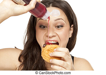 voracious young woman puts the topping on a doughnut