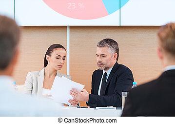 vorbereiten, zu, presentation., sicher, fälliger mann, und, frau, in, formalwear, sitzen tisch, und, anschauen, papier, mit, groß, monitor, auf, seine, kopf, leute, auf, vordergrund