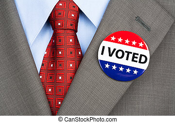 Vote badge on tan suit - A businessman in a tan suit wearing...