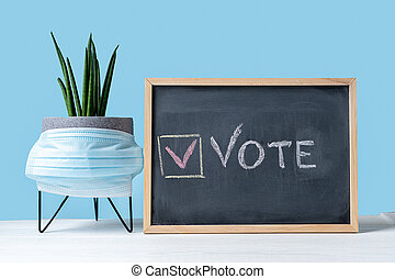 Vote Written On Blackboard. The concept of making choices with medical mask. Presidential and parliamentary elections. Calling for voting, democracy