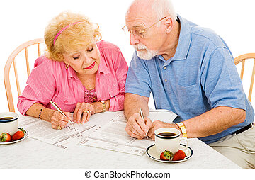 Voting - Comparing Notes - Senior couple filling out their...