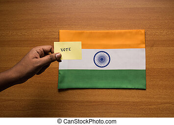 Voting concept - Person holding Hand Written Voting Sticker on India Flag.