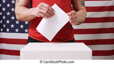 Voting man with American flag - Young man voting and casting...