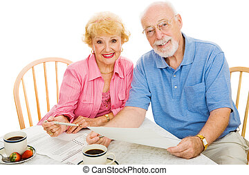 Senior couple using absentee ballots to vote in an election. Isolated on white.