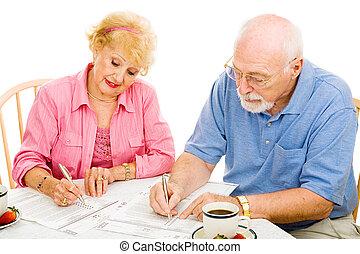 Voting - Seniors Mark Ballots - Senior couple filling out...