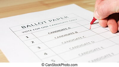 Voting with ballot paper - Voter's hand selecting and ...
