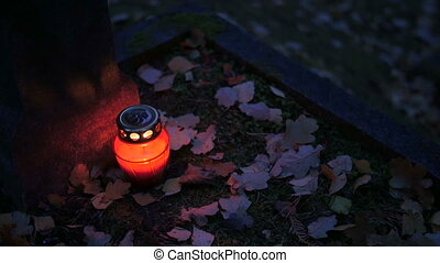 Votive candle on grave - Candle on the tomb, autumn, night....