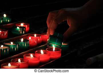 Votive candles in a church - Red and green votive candles in...