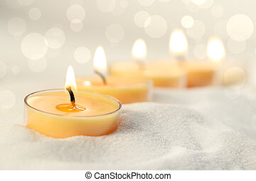 Votive candles in sand lit and arranged for ambiance