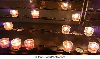 Votive candles lit in some cathedral and standing on some low racks