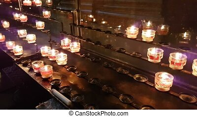 Votive candles standing on some racks in a Christian  Cathedral in Europe