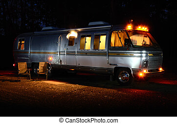 Night time scence with alll the lights at on the inside of a motorhome.