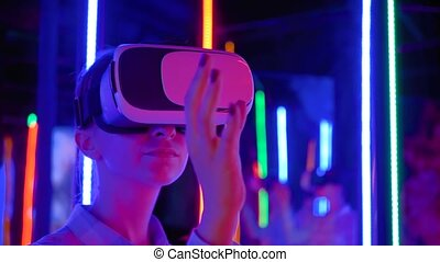 VR concept - woman using virtual reality headset at sci-fi exhibition