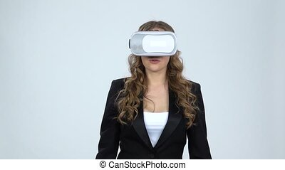 VR concept. Woman with virtual reality goggles on gray...