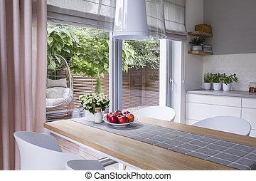 vrai, photo, de, a, moderne, salle manger, intérieur, à, a, table, cliché, pommes, et, vue, sur, a, terrasse, à, a, balançoire
