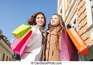 vrienden, shopping., laag hoek overzicht, van, vrolijke , twee, jonge vrouwen, staand, met, hun, hands verheven, en, vasthouden, de, het winkelen zakken