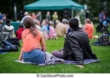vrienden, zitting op het gras, het genieten van, een, buitenshuis, muziek, cultuur, gemeenschap, gebeurtenis, festival.