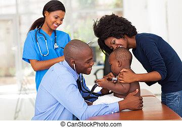 vrolijk, afrikaan, moeder, en, haar, zoon, in, het bureau van de arts, met, mannelijke arts, en, vrouwlijk, verpleegkundige