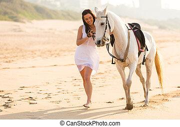 vrolijk, jonge vrouw , wandelende, met, een, paarde, op, strand