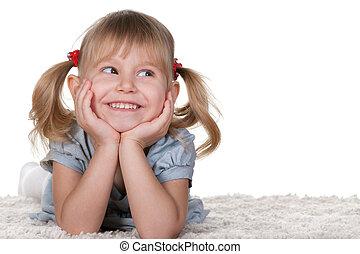 vrolijk, klein meisje, het liggen, tapijt